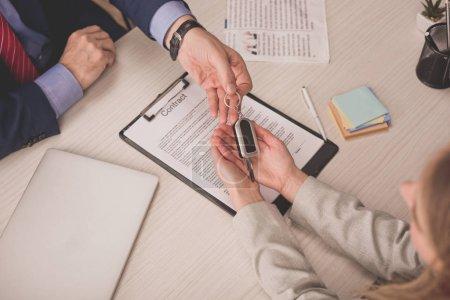 Photo pour Vue de haut de l'agent donnant la clé de voiture au client près du presse-papiers avec contrat - image libre de droit