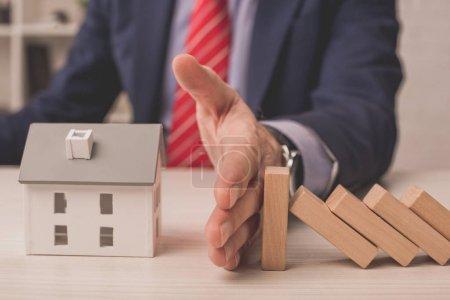 Photo pour Vue recadrée de l'agent mettant la main sur le bureau entre les cubes en bois et le modèle de maison en carton - image libre de droit