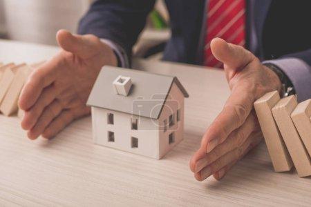 Photo pour Vue recadrée de l'agent mettant les mains sur le bureau entre les cubes en bois et le modèle de maison en carton - image libre de droit