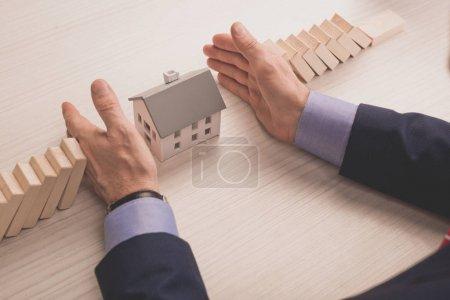 Photo pour Vue en coupe d'un agent immobilier mettant les mains sur la table entre des cubes de bois et un modèle de maison en carton - image libre de droit