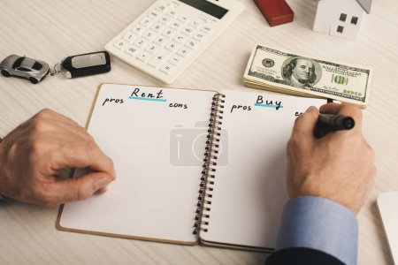 Photo pour Vue en coupe d'un agent écrivant dans un cahier avec location et achat de lettres près de l'argent et calculatrice - image libre de droit