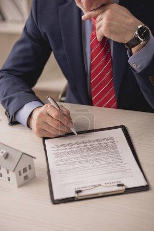Photo pour Vue en coupe d'un agent pensif tenant un stylo près de la planche à reliure avec contrat de location et maquette en carton - image libre de droit