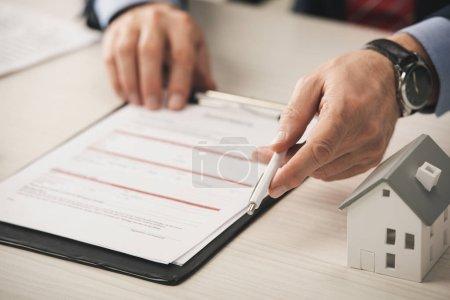 Photo pour Crochet d'un agent tenant un stylo près d'un modèle de porte-papiers et de boîte en carton - image libre de droit