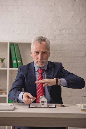 Photo pour Un courtier en immeubles barbu tenant la main au-dessus d'un carton modèle de maison sur un presse-papiers près des clés sur le bureau - image libre de droit