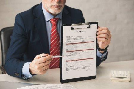 Photo pour Vue en coupe d'un agent barbu tenant un stylo près du presse-papiers avec lettres d'assurance dans le bureau - image libre de droit