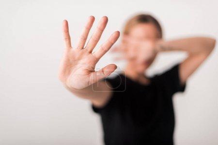 Foto de Enfoque selectivo de la mujer mostrando gesto de stop aislado en blanco - Imagen libre de derechos