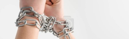 panoramic shot of woman in metallic chains isolated on white, human rights concept