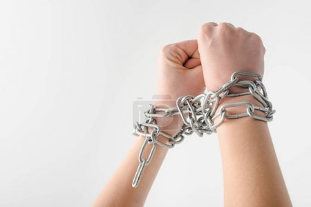 cropped view of woman in metallic chains isolated on white, human rights concept