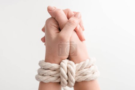 Photo for Cropped view of woman with rope on praying hands isolated on white, human rights concept - Royalty Free Image
