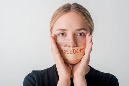 Photo pour Femme avec scotch tape sur la bouche avec liberté lettrage isolé sur blanc, concept des droits de l'homme - image libre de droit