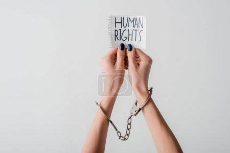 Photo pour Vue recadrée d'une jeune femme menottée sur des mains tenant du papier avec des lettres de droits humains isolées sur du blanc - image libre de droit