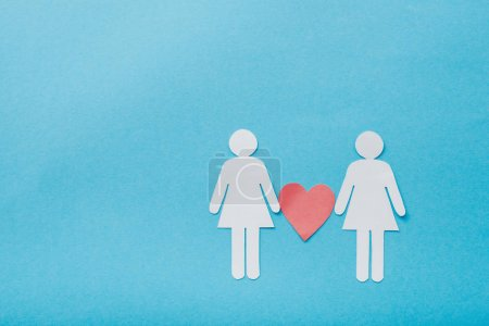 Photo pour Top view of paper cut figures of homosexual couple with heart isolated on blue, sexual equality concept - image libre de droit