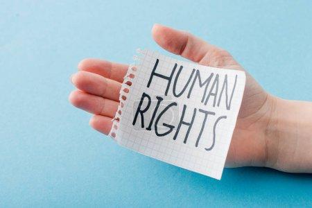 Photo pour Vue recadrée de la femme tenant du papier avec des lettres de droits humains isolées sur bleu - image libre de droit