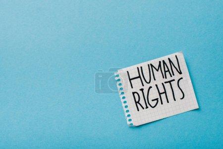 Photo pour Vue du dessus du papier avec lettrage des droits de l'homme isolé sur bleu - image libre de droit