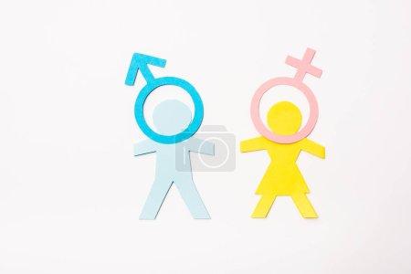Draufsicht auf blaues und gelbes Papier geschnittene Menschen in der Nähe von Genderschildern isoliert auf weißem, sexuellem Gleichstellungskonzept