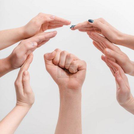 Photo pour Vue recadrée des femmes protégeant la main de l'homme avec le poing serré isolé sur blanc, concept des droits de l'homme - image libre de droit