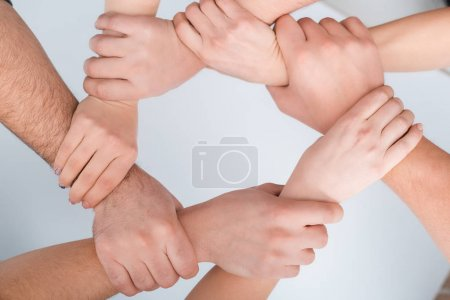 Photo pour Top view of women and man with joined hands together on white, human rights concept - image libre de droit
