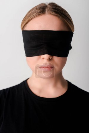 Photo for Blindfolded young woman isolated on white, human rights concept - Royalty Free Image