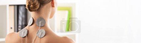 Photo pour Vue arrière de la femme avec électrodes de stimulation électro sur le cou, vue panoramique - image libre de droit