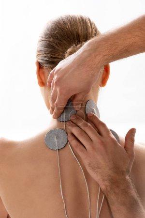 Photo pour Thérapeute tenant électrodes de stimulation sur le cou du patient pendant le traitement d'électrode isolé sur blanc - image libre de droit