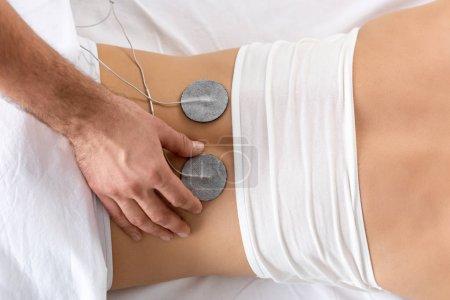 Foto de Vista superior del electrodo de ajuste terapeuta en la espalda del paciente durante la electroterapia en el sofá de masaje. - Imagen libre de derechos