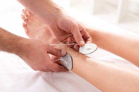 """Photo pour Vue agrandie des électrodes de réglage du thérapeute sur la jambe du patient pendant l """"électrothérapie en clinique - image libre de droit"""