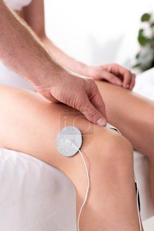 Photo pour Vue croustillante de l'électrode de réglage du thérapeute sur le genou du patient pendant l'électrothérapie - image libre de droit