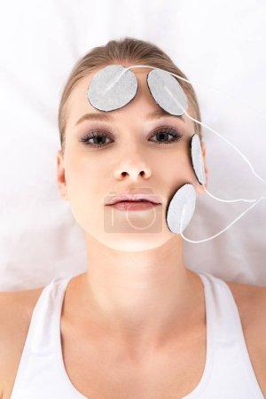 Photo pour Vue du dessus de la fille attrayante regardant la caméra pendant l'électrothérapie faciale sur le canapé de massage - image libre de droit