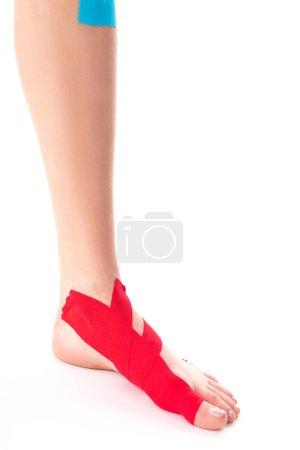 Photo pour Vue recadrée de la jambe femelle avec des bandes de kinésiologie sur fond blanc - image libre de droit