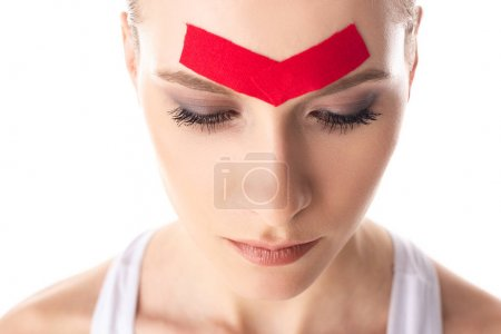 Photo for Beautiful girl with kinesiology tapes on forehead isolated on white - Royalty Free Image