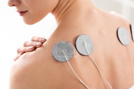 Photo pour Vue recadrée du dos de la jeune femme avec des électrodes pendant le traitement des électrodes en clinique - image libre de droit