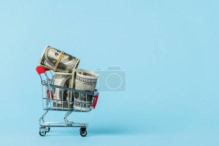 Photo pour Chariot d'achat de jouets avec billets en dollars sur bleu, concept de leasing - image libre de droit