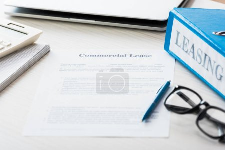 Photo pour Sélectif focus of folder near document with commercial lease lettering on desk - image libre de droit