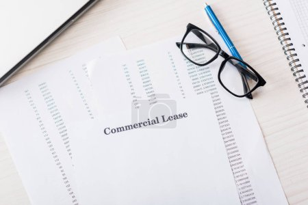 Photo for Top view of document with commercial lease lettering near glasses on desk - Royalty Free Image