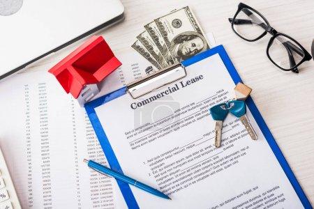 Photo pour Vue du haut du document avec lettre de location commerciale sur le presse-papiers près des clés, argent, modèle de maison, stylo et lunettes - image libre de droit