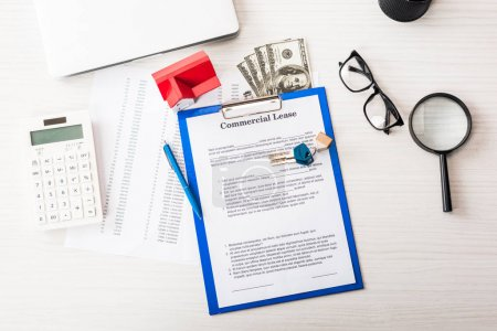 Photo for Top view of document with commercial lease lettering on clipboard near keys, house model, pen, calculator, magnifier, money and glasses - Royalty Free Image