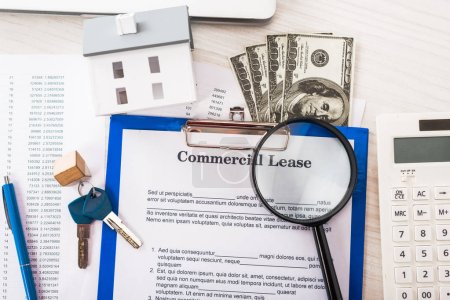 Photo for Top view of document with commercial lease lettering on clipboard near keys, money, house model, pen, calculator and magnifier - Royalty Free Image