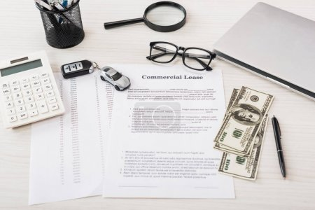 Photo pour Document avec lettre de location commerciale près de la voiture-jouet, argent, calculatrice, loupe, ordinateur portable et lunettes - image libre de droit