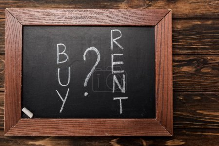 Photo for Top view of chalkboard with buy and rent lettering on wooden surface - Royalty Free Image