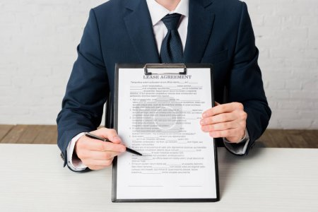 Photo for Cropped view of realtor holding clipboard with lease agreement lettering on document - Royalty Free Image