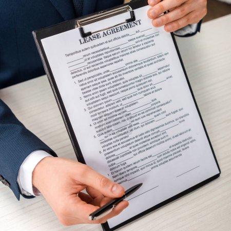 Photo pour Crochet vu d'un homme d'affaires tenant une planche à reliure avec lettre et stylo de contrat de location - image libre de droit