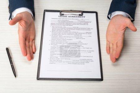 Photo pour Vue en coupe d'un homme d'affaires près de la planche à papiers avec lettre et stylo du contrat de location - image libre de droit