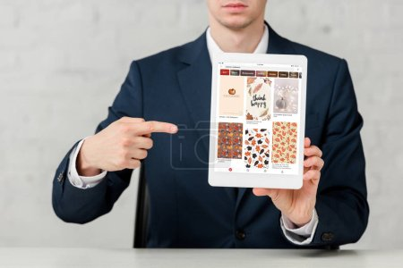 cropped view of realtor in suit pointing with finger at digital tablet with pinterest app on white