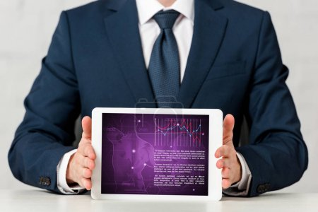 Photo for Cropped view of man in suit holding digital tablet with medical app on white - Royalty Free Image