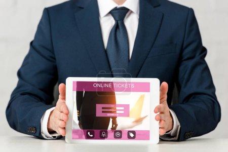Photo pour Crochet vue d'un homme d'affaires tenant une tablette numérique avec des billets en ligne sur écran blanc - image libre de droit