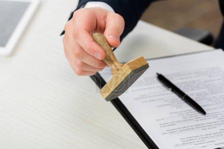Photo pour Vue recadrée de l'agent immobilier tenant le timbre près du presse-papiers et du stylo sur le bureau, concept de location - image libre de droit