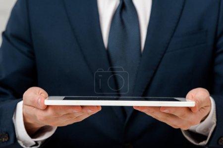 Photo pour Crochet vue d'un homme d'affaires tenant une tablette numérique - image libre de droit