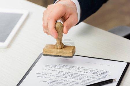 Photo pour Vue recadrée de l'agent immobilier tenant le timbre près du presse-papiers avec document sur la table, concept de location - image libre de droit