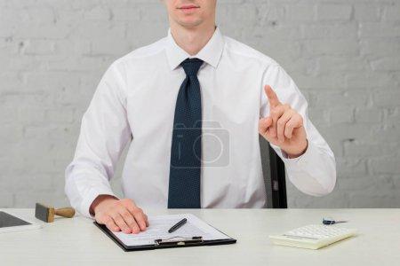 abgeschnittene Ansicht des Maklers im Anzug, der mit dem Finger zeigt, während er am Schreibtisch auf weißem, Leasingkonzept sitzt