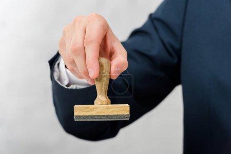 Photo pour Vue recadrée de l'agent immobilier tenant le timbre isolé sur blanc - image libre de droit